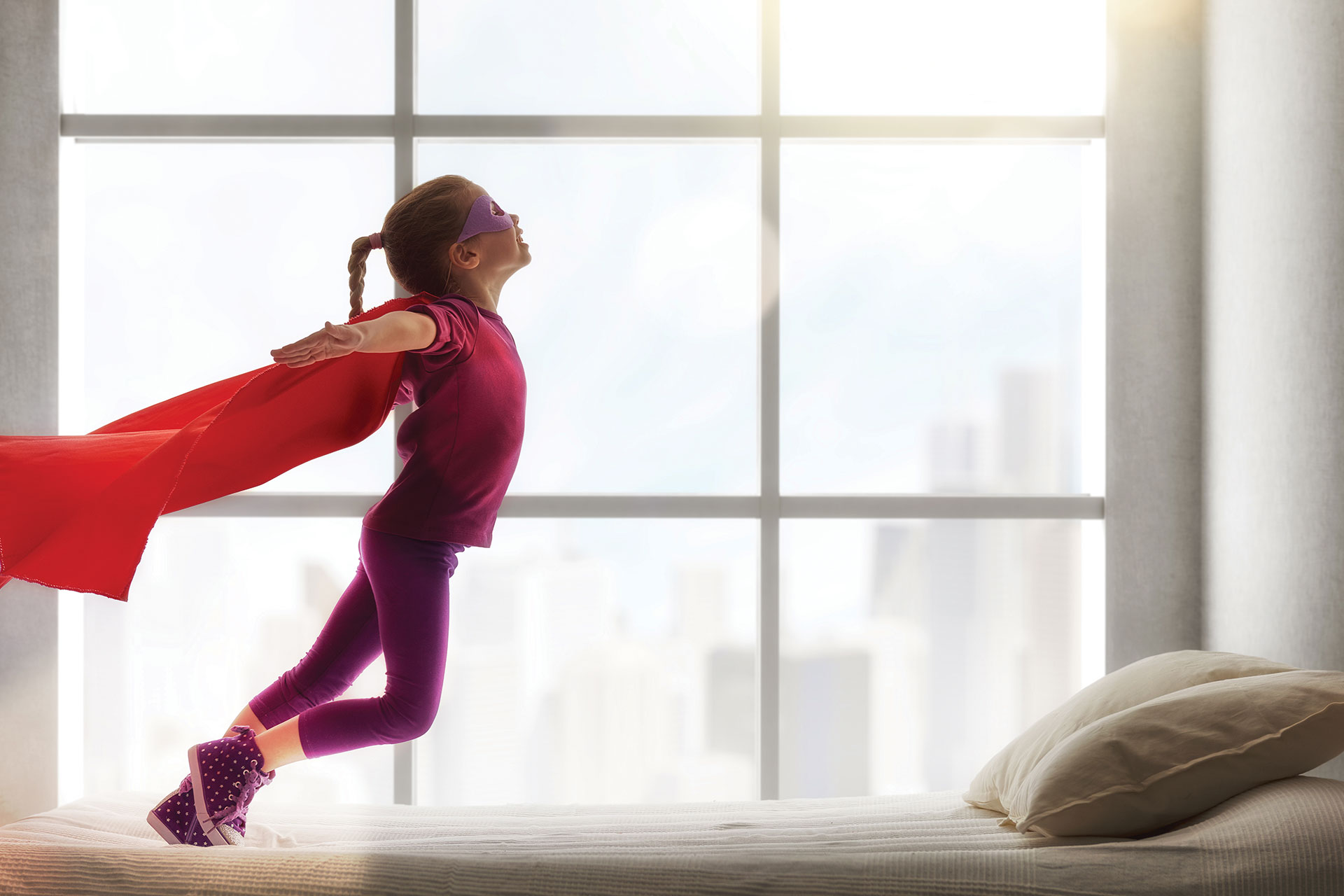 young girl in superhero costume jumping on bed