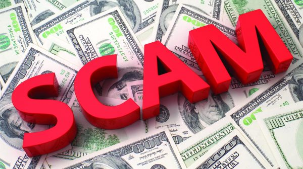 word scam written in red letters on top of a pile of 100 dollar bills